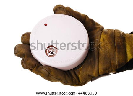 Closeup of firefighters hand holding fire alarm isolated on white - stock photo