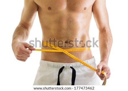 Closeup of fit young man's body. Man measuring his waist with tape measure. Isolated on white background. Diet, fitness, sport and healthy lifestyle concept. - stock photo
