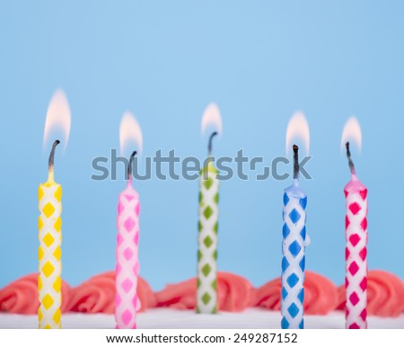 Closeup of five various colored birthday candles on top of a cake - stock photo