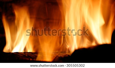 Closeup of flames from the charred wood in the fireplace - stock photo