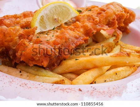 Closeup of flash fried fish and chips on plate with lemon slice - stock photo