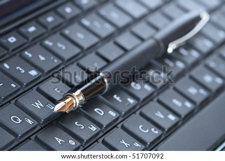 Closeup of fountain pen lying on black computer keyboard