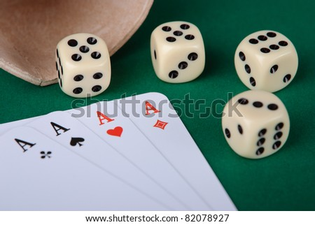 Closeup of four aces and four dices on green background - stock photo