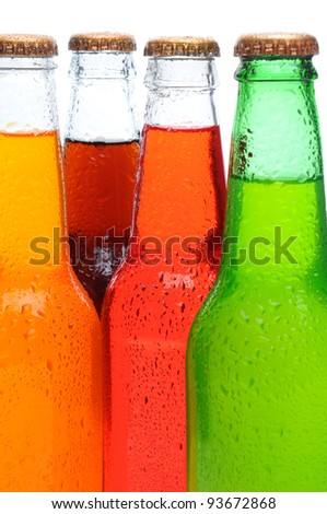 Closeup of four assorted soda bottles with condensation. Vertical format over a white background. - stock photo