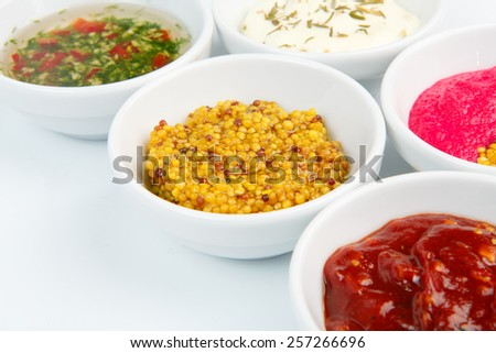 Closeup of french mustard and other sauces in white bowls - stock photo