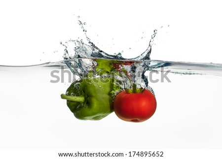 Closeup of fresh and health tomato and Pepper falling into clear water with big splash isolated on white background. Clean eating - stock photo