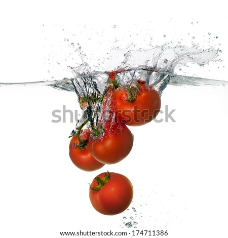 Closeup of fresh and health tomatoes falling into clear water with big splash isolated on white background. Clean eating concept - stock photo