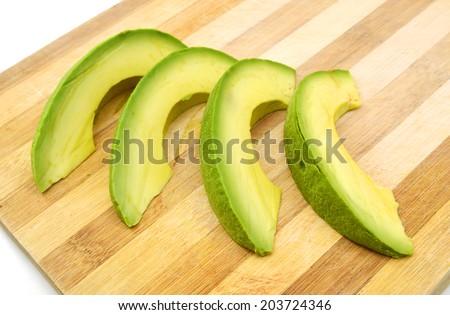 closeup of fresh avocado slices on wooden board - stock photo