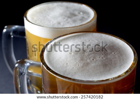 Closeup of Fresh Beer with Foam  in Two Beer Glasses Over Black Background - stock photo