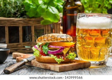 Closeup of fresh burger and a cold beer - stock photo