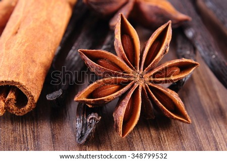 Closeup of fresh star anise, fragrant vanilla pods and cinnamon sticks on wooden surface plank, seasoning for cooking or baking - stock photo