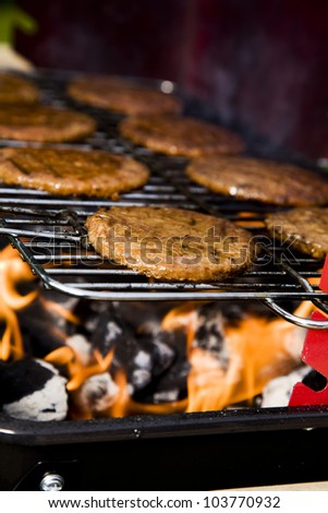 Closeup of fried burgers and meat on grill in fire background - stock photo