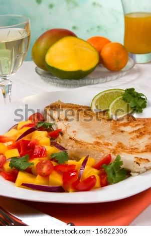 Closeup of fried skate (ray) with mango, cherry tomato and red onion salsa. Fresh fruits, glass of white wine and glass of juice.