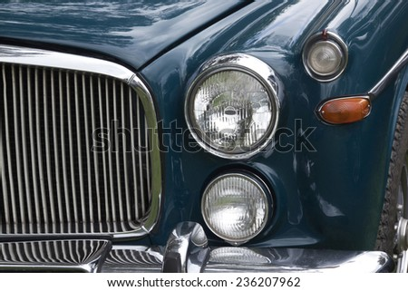 closeup of front end chrome grille and lights of restored vintage classic car - stock photo