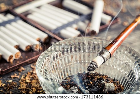 Closeup of fuming a cigarette in the old pipe - stock photo