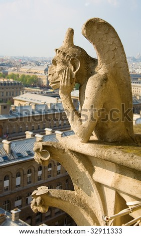 Closeup of gargoyle on the top of Notre-Dame de Paris - stock photo