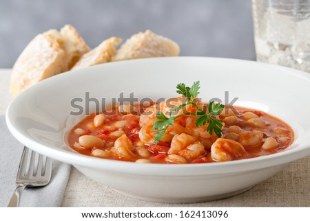 Closeup of garlic shrimp with beans and tomato. - stock photo