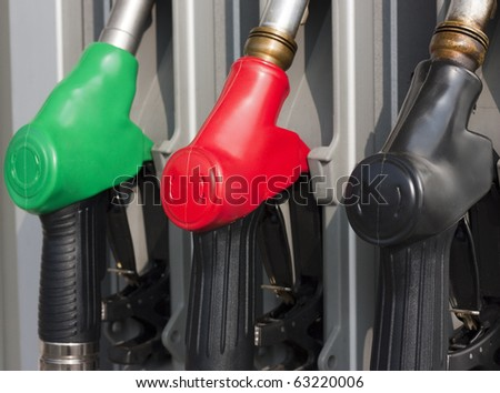 Closeup of Gas Pump Nozzles at Gas Station - stock photo