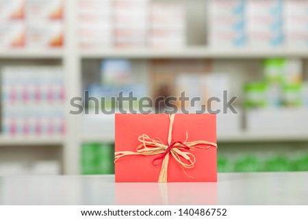 Closeup of gift wrapped in red paper and bow at pharmacy counter - stock photo