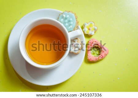 closeup of ginger cookies and cup of tea on light green background - stock photo