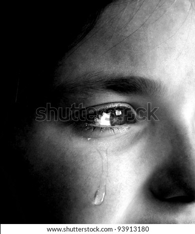Closeup of girl crying with tear rolling down her cheek - stock photo