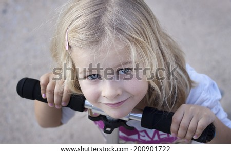 Closeup of girl leaning on handlebar of scooter