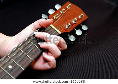 Closeup of girl playing chord on guitar