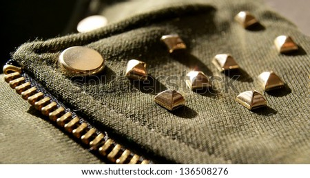 Closeup of girl's jacket with golden metal spikes, swag style - stock photo