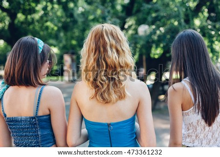 Closeup of girlfriends walking together in the park