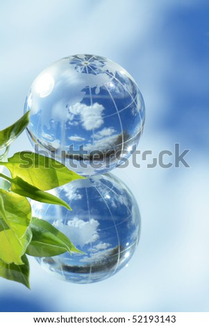 Closeup of glass globe and green leaves lying on mirror background with blue sky and clouds reverberation