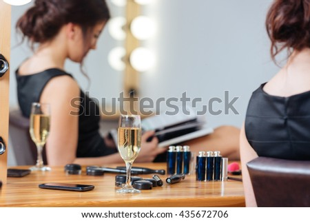 Closeup of glass of champagne standing on the table near young woman reading magazine in dressing room - stock photo