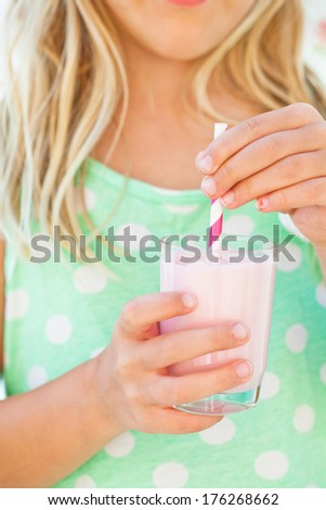 Closeup of glass of smoothie drink with straw held in hand by young girl - stock photo