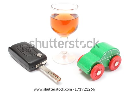 Closeup of glass of wine with car key and old wooden toy car, key car and alcohol, don't drink and drive concept. Isolated on white background