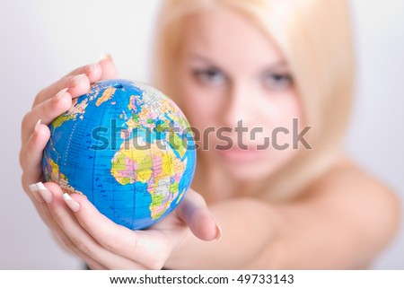 Closeup of globe in the young blonde women`s hands