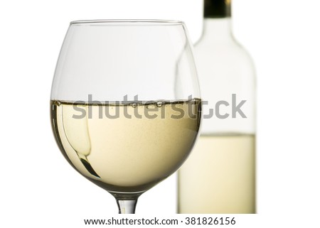 closeup of goblet with white wine and bottle on background - stock photo
