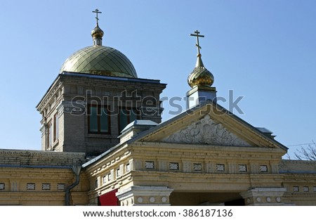Closeup of golden dome of Orthodox church with big cross at blue.