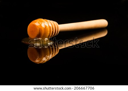 Closeup of golden honey on the wooden spoon on black background