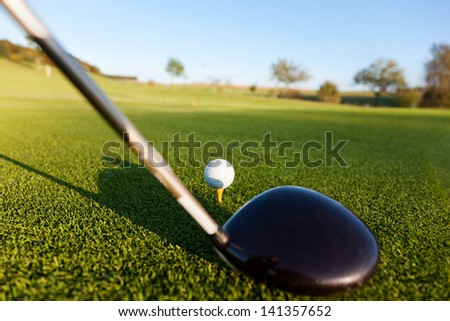 Closeup of golf club and ball on green field - stock photo
