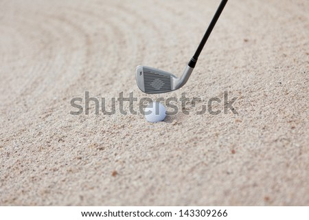 Closeup of golf club and ball on sand - stock photo