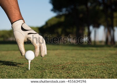 closeup of golf players hand placing ball on tee. beautiful sunrise on golf course landscape  in background - stock photo
