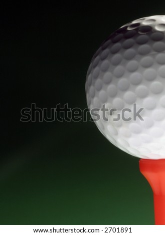Closeup of golfball on red tee against green background - stock photo