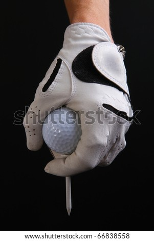 Closeup of golfers gloved hand, golf  ball and golf tee against a black background
