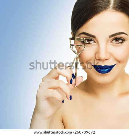 Closeup of gorgeous young woman with makeup with blue lips using lash curler smiling. Beautiful girl applying makeup against blue and white background. Square format, retouched. - stock photo
