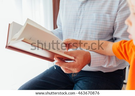 Closeup of grandfather reading a book to his grandson, enjoying a book together.