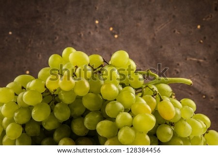 Closeup of green fresh grapes on a dark patterned background - stock photo