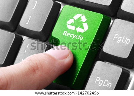 Closeup of green recycle button on the keyboard - stock photo
