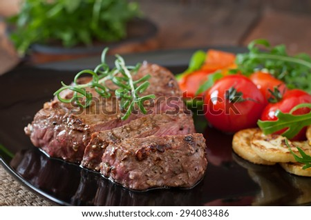 Closeup of grilled beef steak with vegetables - stock photo