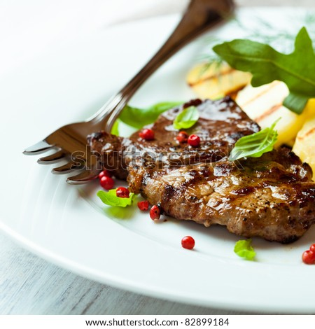 Closeup of grilled juicy steak with basil and pink pepper. Concept for a tasty and healthy meal.