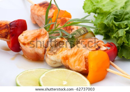 Closeup of grilled salmon and vegatable skewers with fresh tarragon and green salad