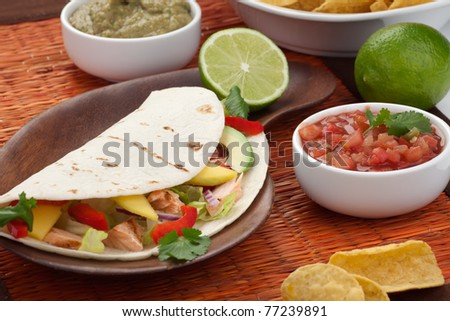 Closeup of grilled salmon fish tacos served with guacamole, fresh tomatoes salsa, and tortilla chips. - stock photo